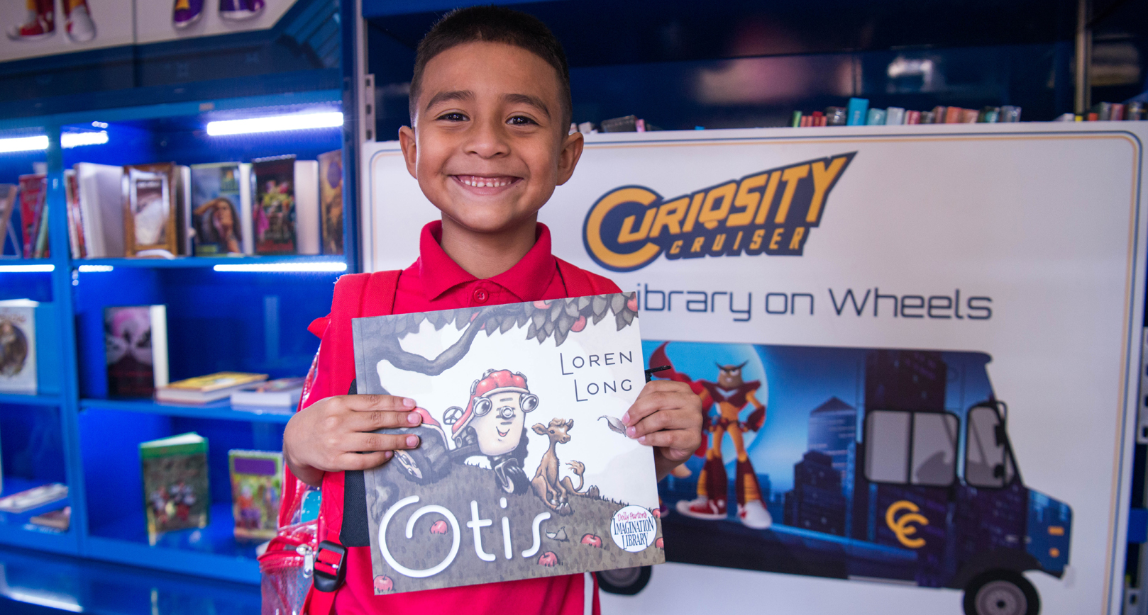 Child receives a free book from the Curiosity Cruiser