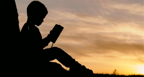 Silhouette of a boy reading a book with a brilliant sunset in the background