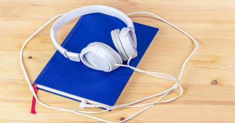 blue book with white headphones laying on top both