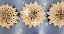 Image of three star decorations made out of paper bags with an image of sparkles over them