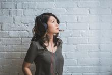 Woman wearing headphones against white wall